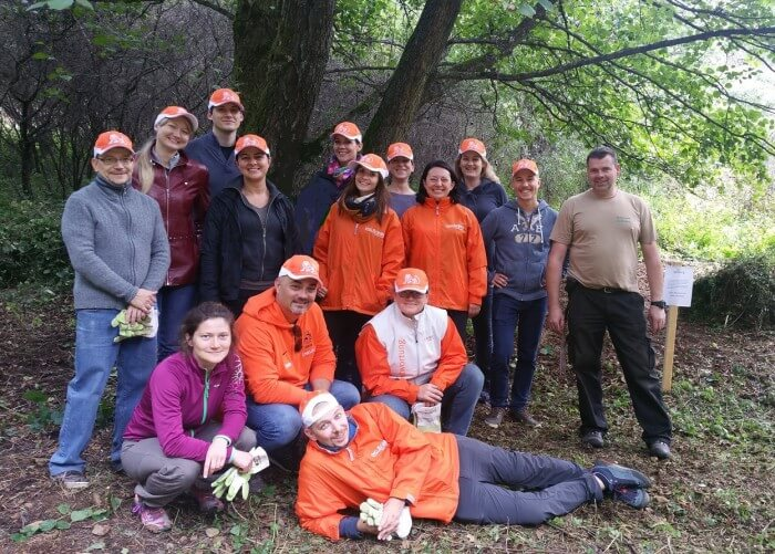 Gruppe in Arbeitskleidung vor Wald