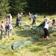 Freiwillige ziehen Mähgut auf Planen von der Fläche