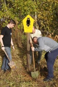 Drei Männer stellen NSG-Schild im Gelände auf