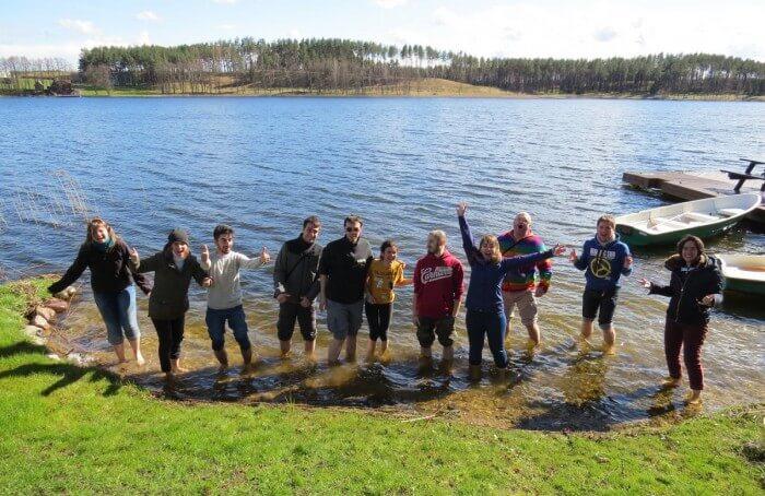 Gruppe junger Menschen am Ufer eines Sees
