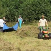 Menschen arbeiten auf Wiese mit Balkenmäher und Planen zum Abtransport des Mähgutes