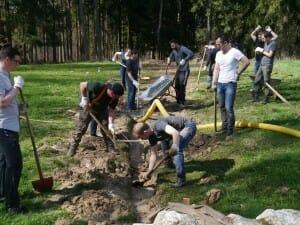 Mehrere Männer schaufeln einen Graben für ein Drainagerohr